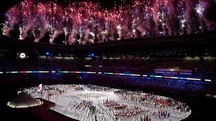 Sous les feux d'artifice et les multiples films d'animation de la cérémonie d'ouverture, les athlètes se sont regroupés au centre de l'enceinte.Le drapeau olympique a ensuite fait son entrée au milieu des délégations internationales présentes dans le Stade national olympique. (JEFF PACHOUD / AFP)