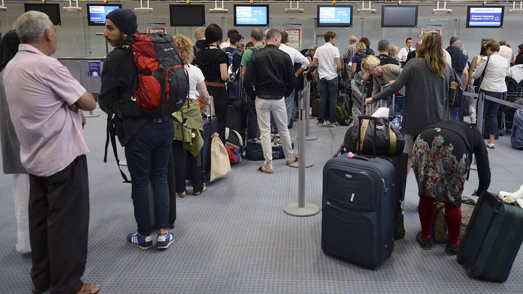 Des passagers attendent au comptoir Air France de l'aéroport de Marseille-Marignane, le 15 septembre 2014. (BORIS HORVAT / AFP)
