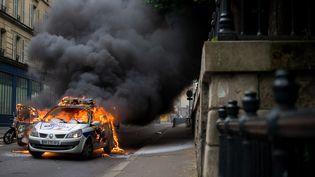 """Le véhicule de police incendié à Paris mercredi 18 mai 2016, en marge du rassemblementdes forces de l'ordre contre la """"haine anti-flic"""". (JAN SCHMIDT-WHITLEY / NURPHOTO / AFP)"""