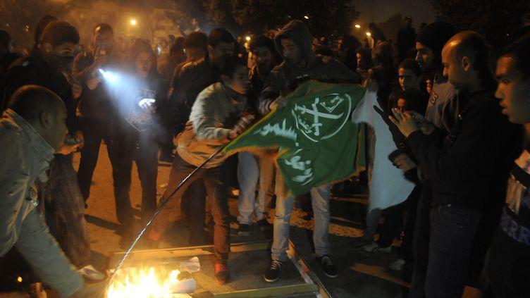 Des opposants au président égyptien Mohamed Morsi brûlent un drapeau des Frères musulmans, le parti dont il est issu, le 6 décembre 2012 au Caire (Egypte). ( AFP )