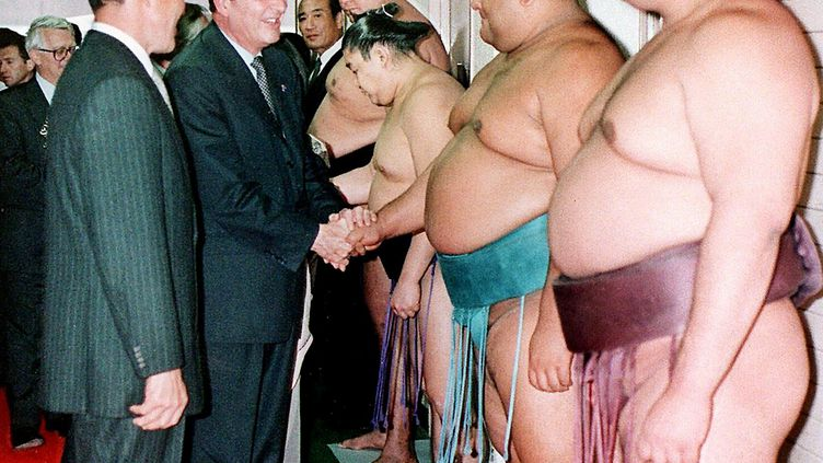Le président Chirac en novembre 1996, à Fukuoka, au Japon félicitant les lutteurs avant un grand match. (JIJI PRESS / AFP)