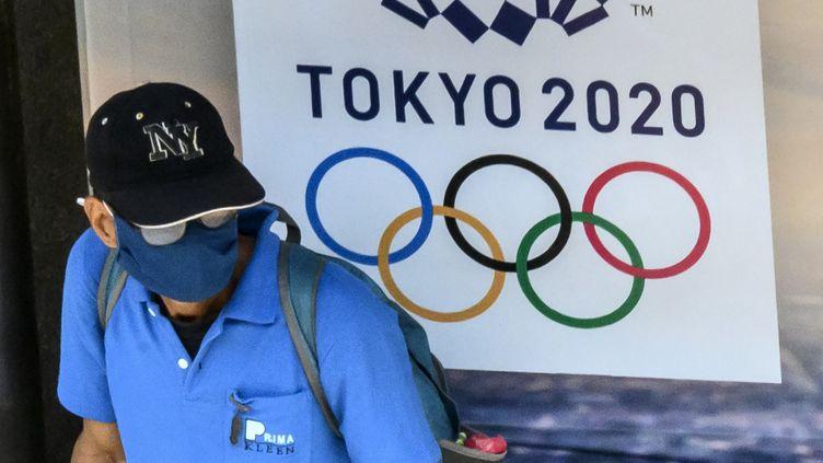 Un homme porte un masque de protection, devant le logo des jeux olympiques de Tokyo 2020. (MLADEN ANTONOV / AFP)