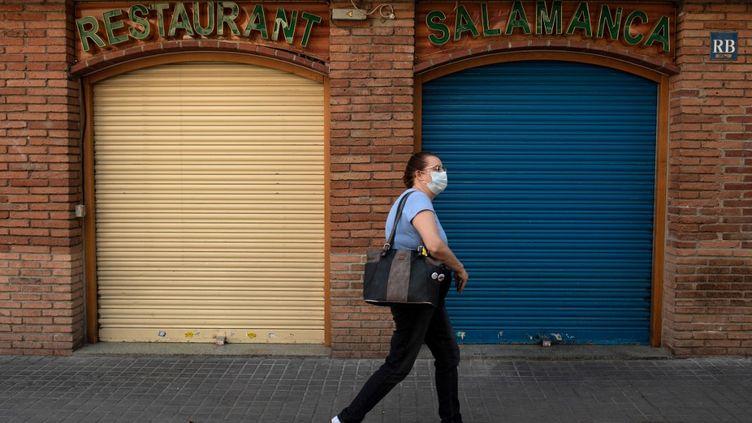 Une femme portant un masque dans une rue de Barcelone (Catalogne, Espagne), le 13 mai 2020. (JOSEP LAGO / AFP)