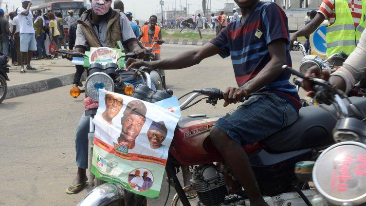 Deux jeunes font campagne pour le présidentMuhammadu Buhari, le président sortant et candidat à sa propre succession, au guidon de leur moto dans les rues de Lagos au Nigeria le 9 février 2019. (ADEKUNLE AJAYI / NURPHOTO)