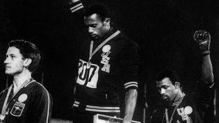 Le 16 octobre 1968, Tommie Smith et John Carlos lèvent un poing ganté de noir sur le podium du 200 mètres pour dénoncer les inégalités raciales. (EPU / AFP)
