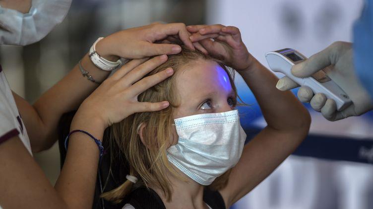 Un employé vérifie la température d'une jeune passagère avant d'embarquer pour un vol pour Paris, à l'aéroport de Tocumen, au Panama, le 11 mai 2020. (LUIS ACOSTA / AFP)