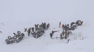 Des membres des services d'urgence creusent dans la neige autour d'au moins trois véhicules renversés, près de la ville de Bahcesehir, dans la province de Van, à l'est de la Turquie, le 5 février 2020. (DHA / AFP)