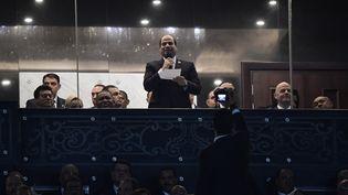 Derrière une vitre de protection, le président égyptien Abdel Fattah al-Sissi prononce un discours lors de la cérémonie d'ouverture du match de football 2019 de la Coupe d'Afrique des Nations opposant l'Egypte et le Zimbabwe au Stade international du Caire, le 21 juin 2019. (JAVIER SORIANO / AFP)