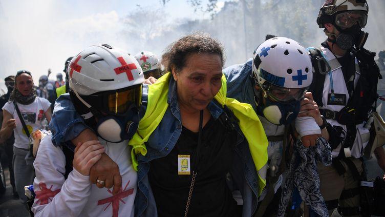 """Des """"street-medics"""" accompagnent une """"gilet jaune"""" lors de la manifestation organisée à Paris, samedi 20 avril 2019. (ANNE-CHRISTINE POUJOULAT / AFP)"""