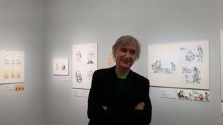 Plantu, dessinateur et caricaturiste, devant ses dessins exposés à la Bibliothèque nationale de France, à Paris en mars 2018. (ANNE CHÉPEAU / FRANCEINFO)