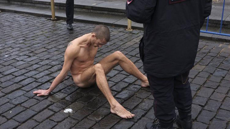 Des policiers russes encerclent l'artistePiotr Pavlenski, qui a cloué la peau de ses testicules entre des pavés de la place Rouge, à Moscou(Russie),le 10 novembre 2013. (MAXIM ZMEYEV / REUTERS)