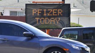 Des automobilistes passent devant un panneau annonçant des doses du vaccin contre le Covid-19 de Pfizer disponible, à Cal State Los Angeles en Californie, le 3 mai 2021. (FREDERIC J. BROWN / AFP)