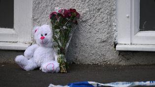Une peluche et un bouquet de fleurs ont été déposés au sol, le 23 mai 2017, près du lieu de l'attentat perpétré à Manchester, la veille. (OLI SCARFF / AFP)