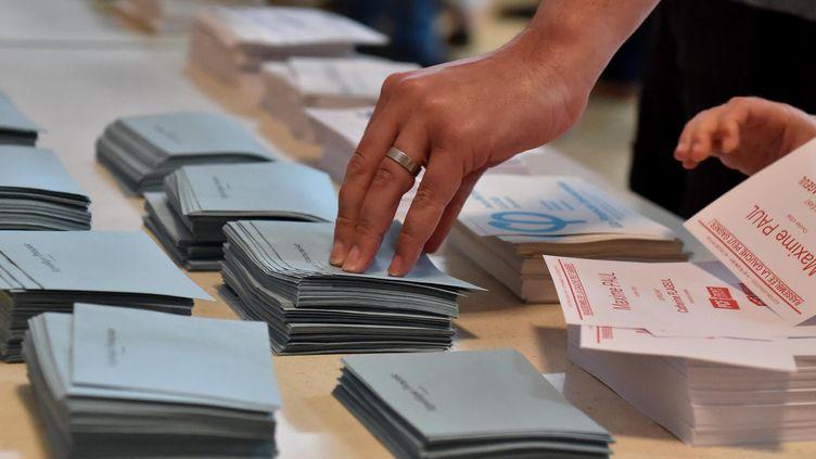Un électeur prend des bulletins de vote lors du premier tour des législatives à Carhaix (Finistère), le 11 juin 2017. (MAXPPP)