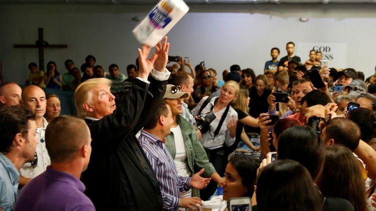 Donald Trump distribuant à sa façon des rouleaux de papier essuie-tout à Puerto Rico, le 3 octobre 2017. (JONATHAN ERNST / REUTERS)