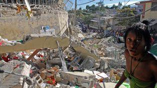 Une jeune femme ère, hagarde, au milieu de ruines d'un immeuble de Port-au-Prince, le 13 janvier 2010. La veille, un séisme d'une magnitude de 7,3 sur l'échelle de Richter a ravagé la capitale du pays, faisant plusde 300 000 morts et autant de blessés. (THONY BELIZAIRE / AFP)