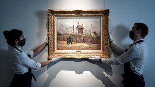 """Deux personnes accrochent le tableau """"Scène de rue à Montmartre"""", un Van Gogh qui sera mis en vente à Paris en mars. (STEPHANE DE SAKUTIN / AFP)"""