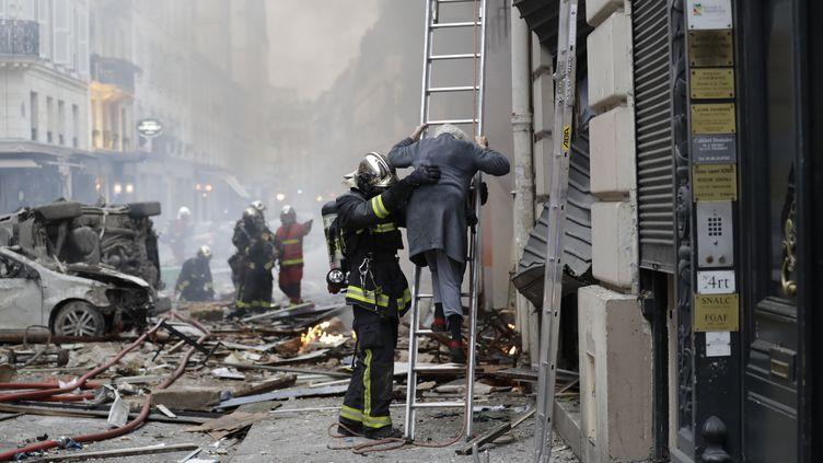 Un pompier aidant une sinistrée de la rue de Trévise, à Paris, le 12 janvier 2019. (THOMAS SAMSON / AFP)
