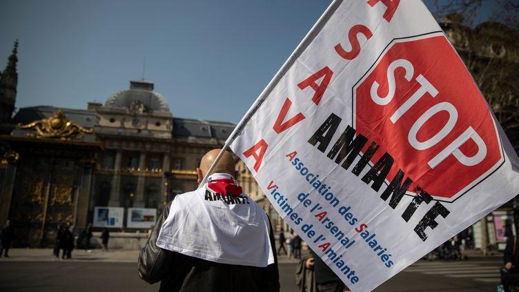 """Un manifestant tient un drapeau """"Stop Amiante"""" devant le Palais de justice de Paris, le 22 mars 2019. (THOMAS SAMSON / AFP)"""