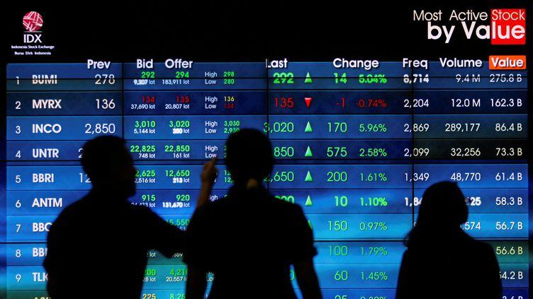Des visiteurs regardent un tableau d'échanges boursiers, le 8 novembre 2016, à Jakarta (Indonésie). (IQRO RINALDI / REUTERS)