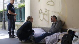 Un membre de l'unité d'assistance aux sans abri de Paris vient à la rencontre d'un SDF, le 21 août 2014, à Paris. (THOMAS SAMSON / AFP)