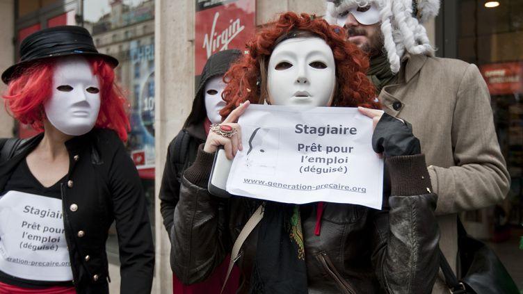 Affublé d'un masque blanc, des membres du collectif Génération précaire manifestent devant le Virgin Megastore des Champs-Elysées à Paris, le 13 novembre 2012. (CITIZENSIDE.COM / AFP)