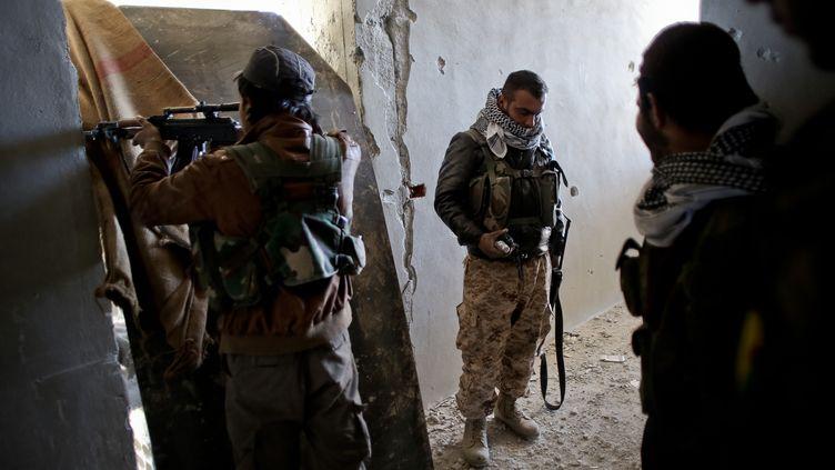 Des combattantskurdes tiennent une position lors de combats face à Daech à Ain al-Arab, en 2014. (AHMED DEEB / AFP)