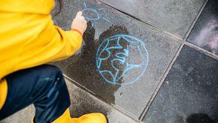 Une petite fille dessine un soleil sur le sol de la place de la République à Paris, le 27 janvier 2019, lors d'une manifestation pour la sauvegarde du climat. (LAURE BOYER / HANS LUCAS / AFP)