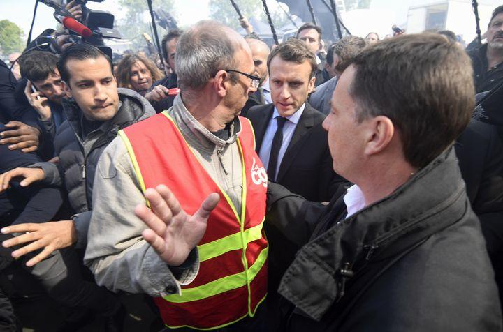 """Le 26 avril 2017, à l'usine Whirlpool d'Amiens (Somme) menacée de fermeture, Emmanuel Macron est accueilli par des huées etdes chants au son de """"Marine, présidente !"""". A ses côtés, Alexandre Benalla est là pour assurer sa sécurité. (ERIC FEFERBERG / AFP)"""