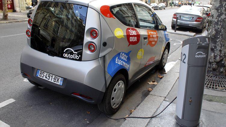 Une Autolib' branchée à sa borne de rechargement, à Paris, le 2 décembre 2011. (PATRICK KOVARIK / AFP)