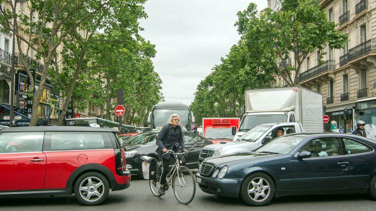 Un vélo au milieu de voitures à Paris en 2015. (BRUNO LEVESQUE / MAXPPP)