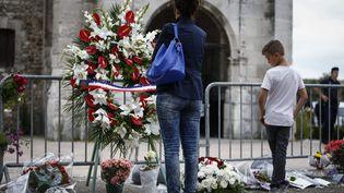 Des personnes se recueillent devant l'église de Saint-Etienne-du-Rouvray (Seine-Maritime), cible d'une attaque terroriste la veille, le 27 juillet 2016. (MAXPPP)