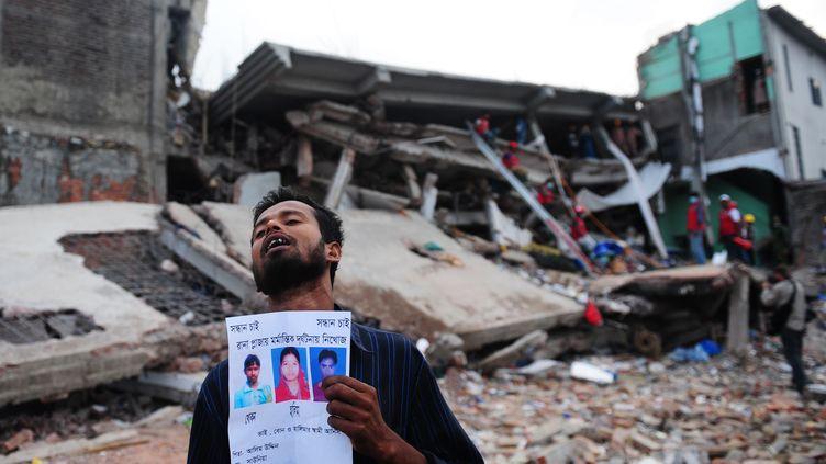 Le 28 avril 2013, un homme brandit la photo de ses proches devant l'immeuble abritant des ateliers textiles qui s'est effrondré près de Dacca au Bangladesh. (MUNIR UZ ZAMAN / AFP)