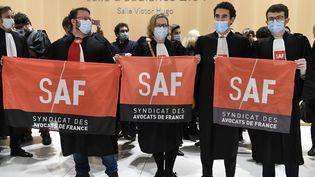 Des membres du syndicat des avocats de France (SAF) opposés à l'usage de la visioconférenceau procès des attentats de janvier 2015, le 23 novembre 2020, au tribunal judiciaire de Paris. (BERTRAND GUAY / AFP)