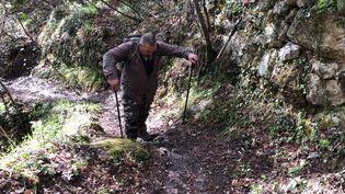 Michel Daigneausur le sentier de randonnéequi lui permet d'atteindre son domicile dans le hameau de Sainte-Sabine à Sospel (Alpes-Maritimes), le 4 avril 2019. (LOUISE HEMMERLE / FRANCE INFO)