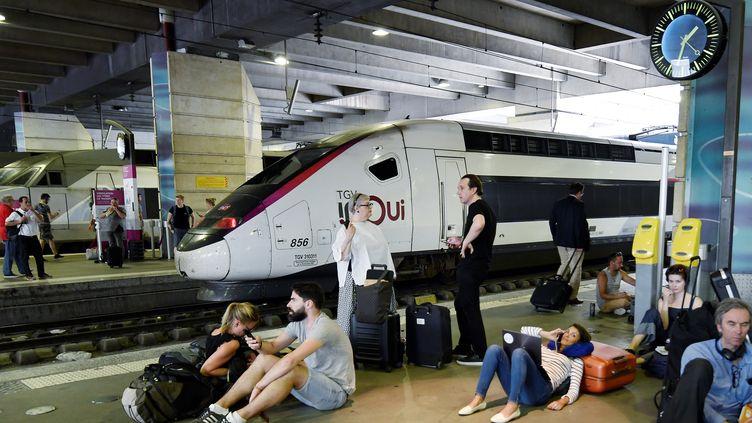 Des voyageurs attendent leur train à la gare Montparnasse, à Paris, le 27 juillet 2018. (GERARD JULIEN / AFP)