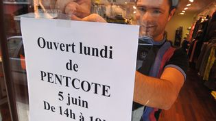 Affiche d'ouverture d'un magazin le lundi de Pentecôte. (MYCHELE DANIAU / AFP)