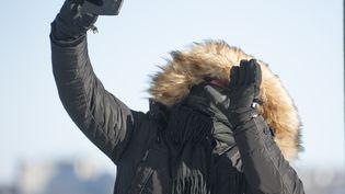 Une personne emmitoufléedans son manteau épais se prend en selfie, à Quebec (Canada), le 27 décembre 2017, pendant qu'une vague de froid touche l'Amérique du Nord, avec des températures qui sont décendues jusqu'à -42,8 degrés au Canada. (ALICE CHICHE / AFP)