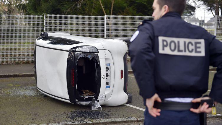 Une voiture vandalisée durant une manifestation de lycéens à Nantes. (LOIC VENANCE / AFP)