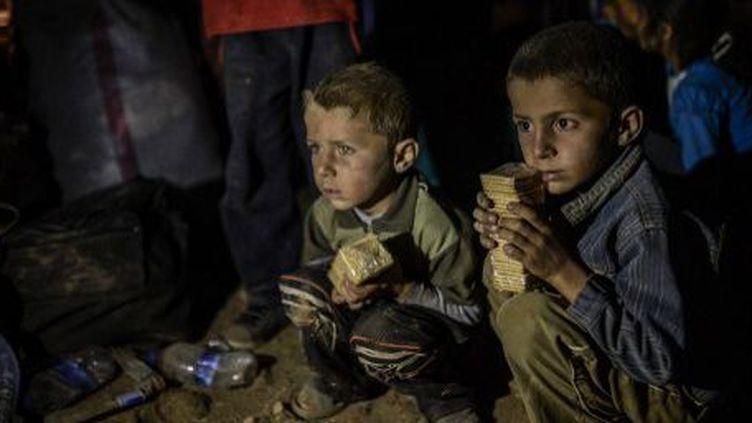Sanliurfa (Turquie) le 21 septembre 2014 : Enfants kurdes syriens, attendant d'entrer dans la ville de Suruc au sud-est de la Turquie.  (AFP PHOTO/BULENT KILIC)