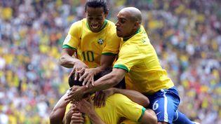 Les joueurs du Brésil Ronaldo (de dos), Roberto Carlos (à droite)et Ronaldinho célèbrent un but lors de leur 8e de finale contre le Ghana, à Dortmund (Allemagne), le 27 juin 2006. (MEXSPORT / AFP)