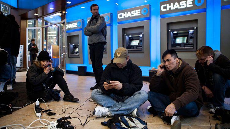 Certains new-yorkais victime de ces coupures d'électricité se retrouvent dans des banques et des magasins qui mettent des multiprises à leur disposition. (ANDREW BURTON / GETTY IMAGES NORTH AMERICA / AFP)