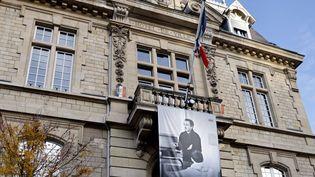 Une photo de Samuel Paty déroulée sur la façade de l'hôtel de ville de Conflans-Saint-Honorine (Yvelines) où il enseignait, le 3 novembre 2020. (Thomas COEX / AFP)