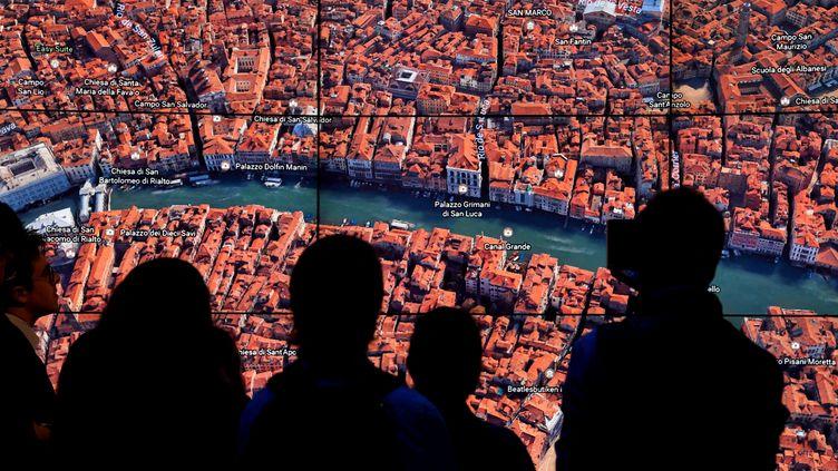 Des personnes regardant Venise sur Google Earth alors que Google Earth dévoilait une nouvelle version de l'application, le 18 avril 2017 lors d'un événement au Whitney Museum of Art de New York (TIMOTHY A. CLARY / AFP)