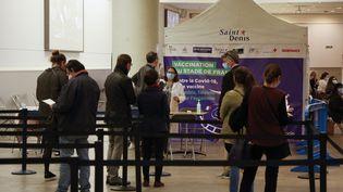 Des personnes attendent de recevoir une dose de vaccin contre le Covid-19 au Stade de France à Saint-Denis, dans le nord de Paris, le 23 avril 2021. (LUDOVIC MARIN / AFP)