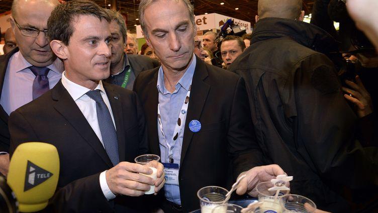 Le Premier Ministre Manuel Valls boit un verre de lait avec Thierry Roquefeuil, le président des éleveurs laitiers au Salon de l'agriculture, lundi 29 février, à Paris. (MIGUEL MEDINA / AFP)