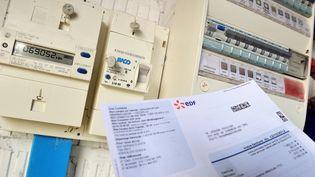 Une facture d'un fournisseur d'électricité devant un compteur. (Illustration). (PHILIPPE HUGUEN / AFP)