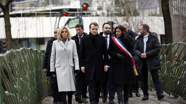 Emmanuel Macron entouré de son épouse Brigitte et de la maire de Paris Anne Hidalgo, sur les lieux de la mort du policier Ahmed Merabet, dimanche 7 janvier 2018. (CHRISTOPHE ENA / AFP)
