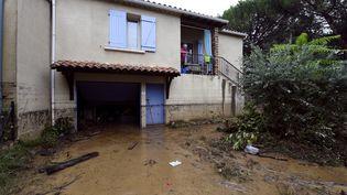 Une vieille dame regarde sa cour inondée, à Lamalou-les-Bains, dans l'Herault, le 18 septembre 2014. (PASCAL GUYOT / AFP)