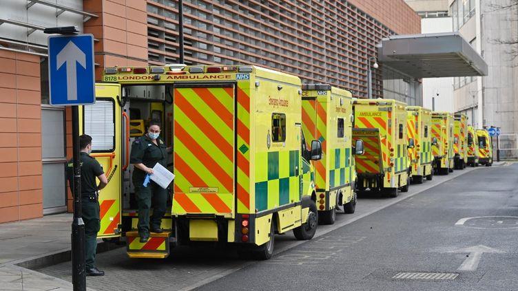 Des ambulances patientent devant un hôpital de Londres (Royaume-Uni), le 3 janvier 2021. (JUSTIN TALLIS / AFP)